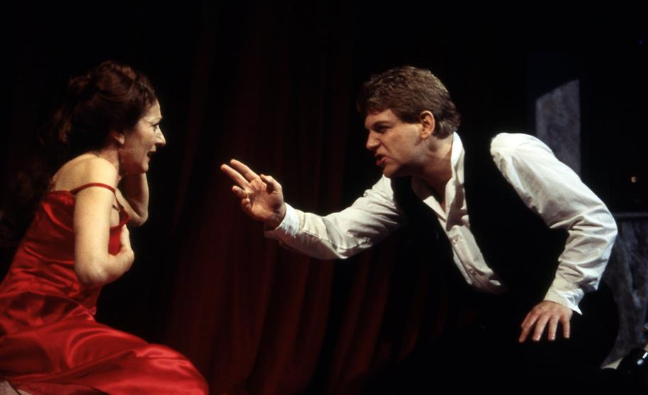Gertrude wearing a red satin evening gown is confronted by her son Hamlet, who points at her with his right hand