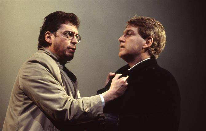 Horatio (Rob Edwards) wearing glasses grabs his friend Hamlet (Kenneth Branagh) by the lapels