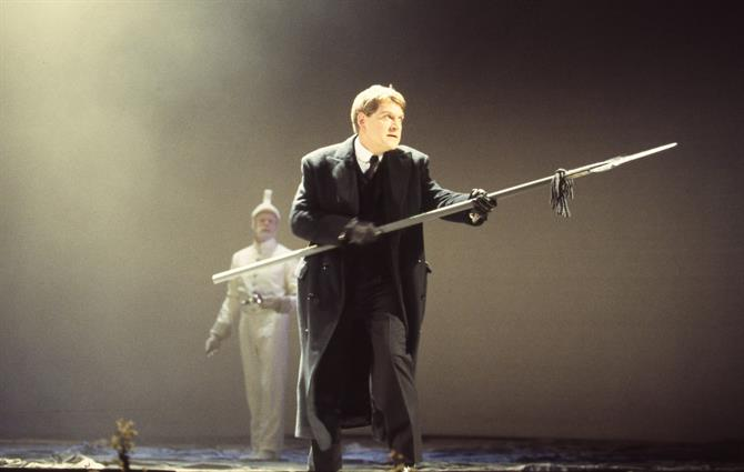 Hamlet (Kenneth Branagh) brandishes a halberd as a ghost-like figure in white stands behind him