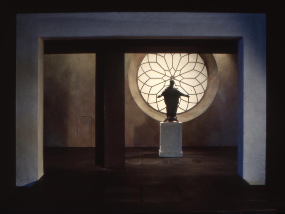 Model of a stage set showing a statue with open arms on a plinth in front of a round window with floral tracery