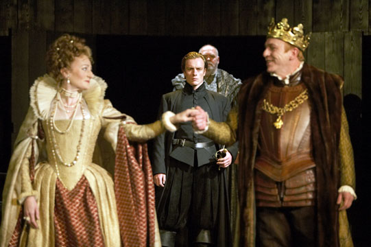 The cast of Hamlet on stage, in the foreground King and Queen hold hands and appear happy