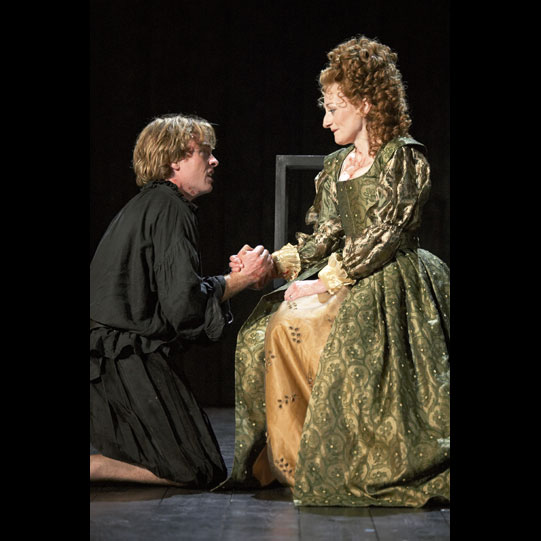 Hamlet kneels on the floor holding his Mothers hand