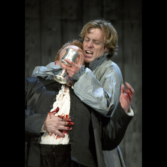 Two men on stage, Hamlet forces a wounded Claudius to drink out of the poisoned wine cup
