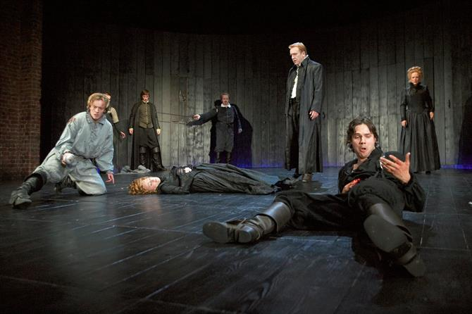 Laertes lies on the floor after being wounded by Hamlet at Ophelia's funeral