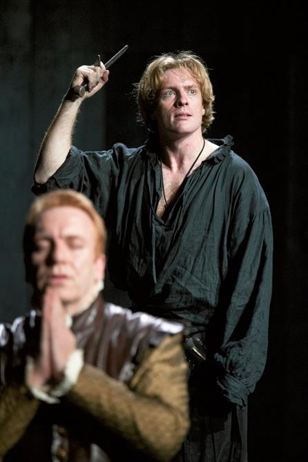 Two men on stage: one on his knees praying, the other standing behind him with a dagger in hand