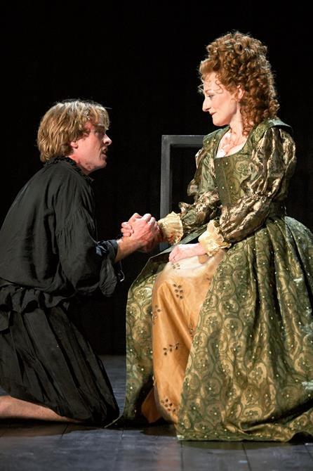 Hamlet kneels on the floor holding his mother's hand
