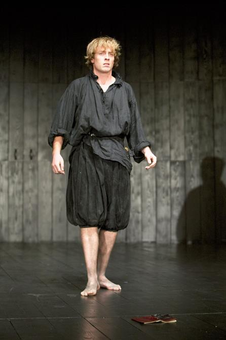 Hamlet wears short black trousers and a loose shirt. A book lies face down on the ground in front of him