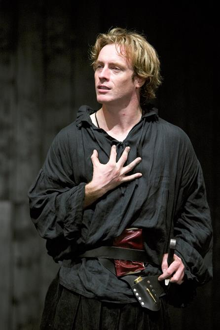 Hamlet on stage in loose black clothes