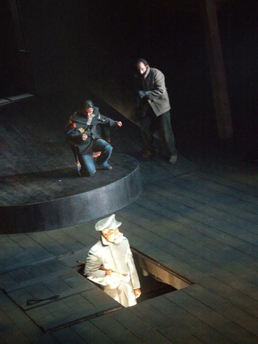 Two men look shocked as another man rises out of a trapdoor in the stage, lit with bright white light