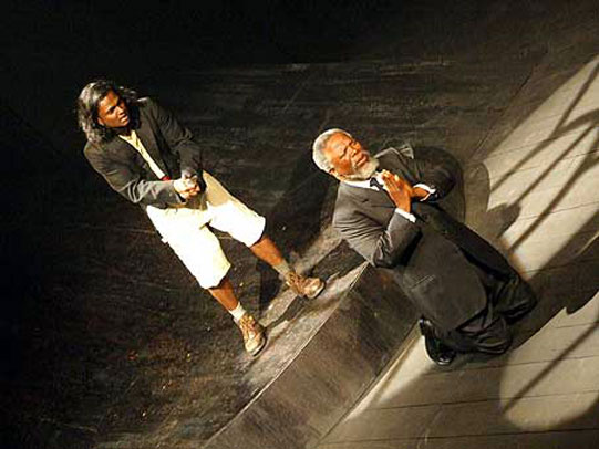 Two men on stage, one kneeling in prayer the other stands with a knife in hand behind