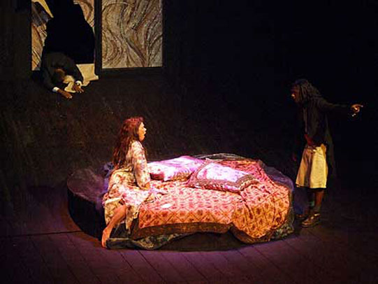 A man and woman on stage, woman sits on bed and man stands almost covered by darkness