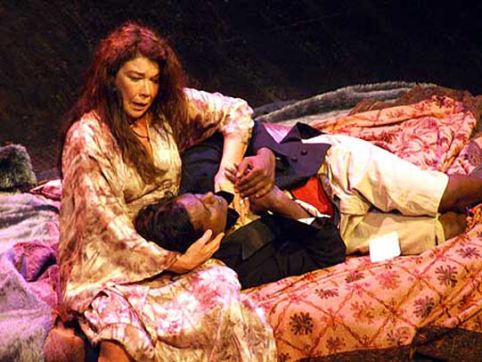 Gertrude holds Hamlet head in her arms whilst both sit on a bed