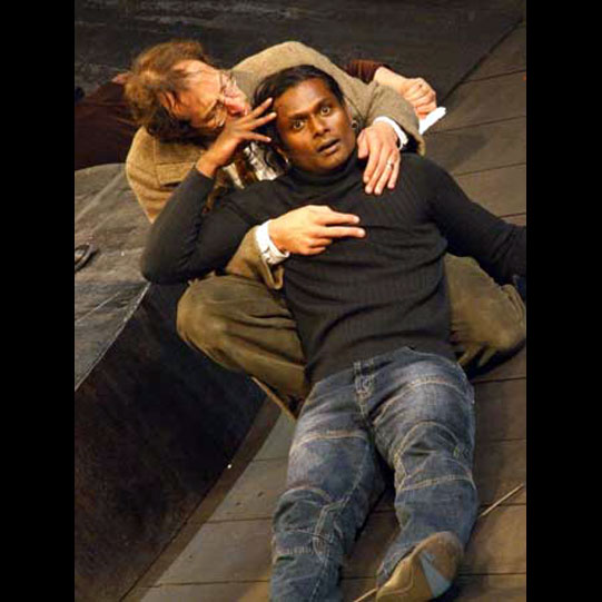 Two men on stage lying on the floor