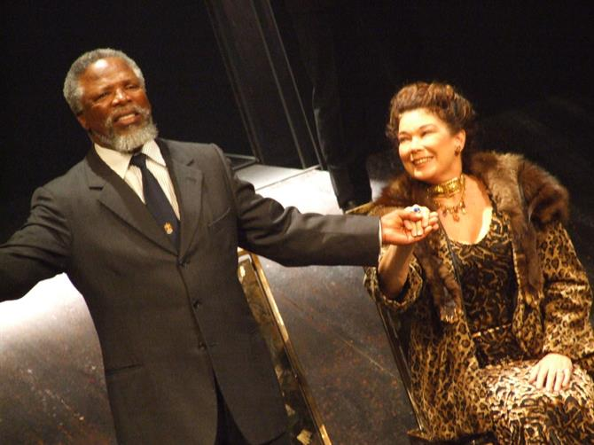 Man and woman on stage holding hands