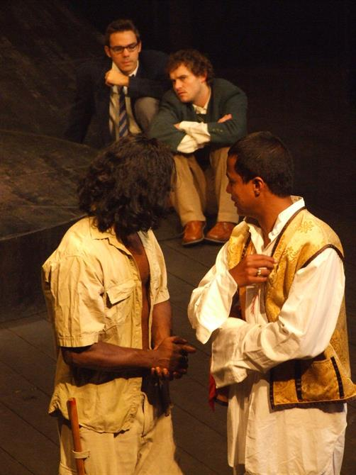 Four men on stage, two looking back and two sitting down, all deep in thought