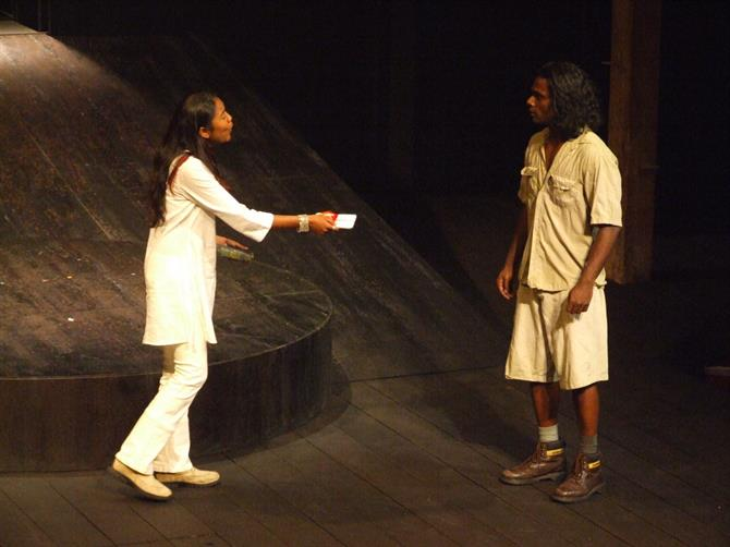 A woman all in white holds out a piece of paper to a man in shorts