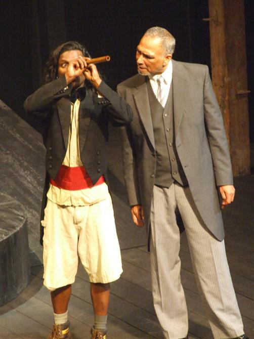 Two men on stage, one with a small telescope-like object