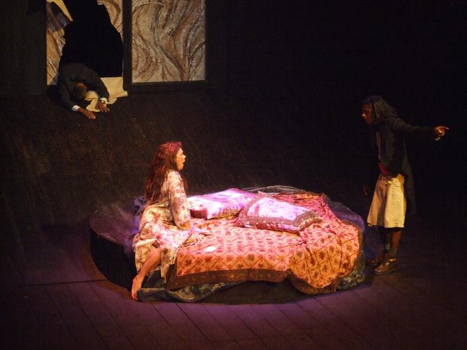 A woman sits on a round bed, with a man standing nearby, almost covered by darkness