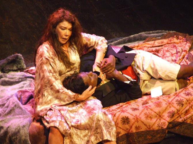 Gertrude holds Hamlet's head in her arms whilst both sit on a bed