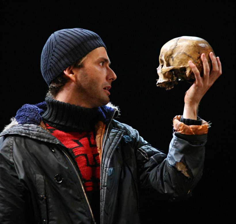 Hamlet holds a skull in front of his face