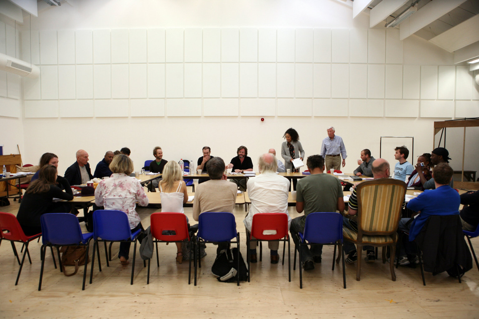 Actors sit around a table reading through the script