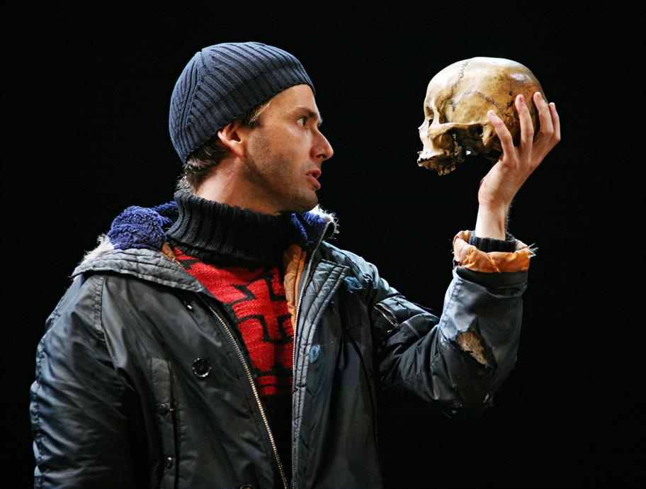 Hamlet in an anorak and beanie hat holds a skull to his face