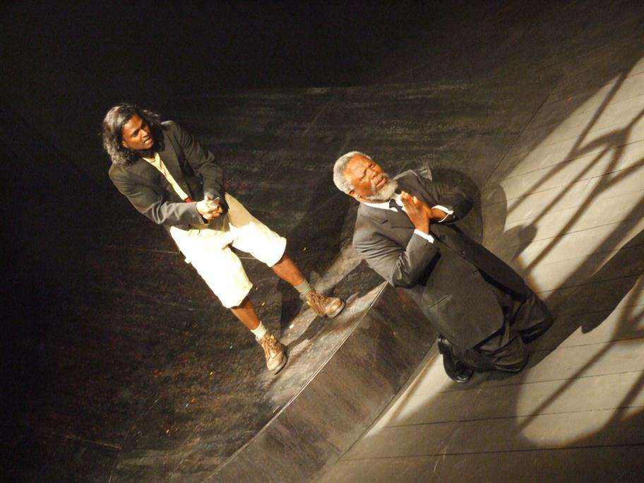 Two men on stage one kneeling in prayer and other with a dagger in hand