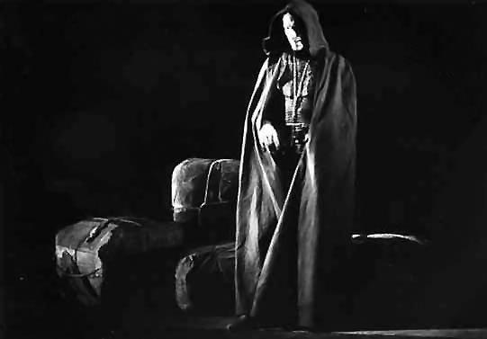 Man in cloak on stage.