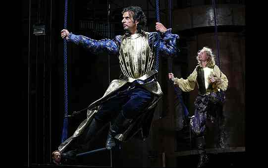Two men in purple clothes and golden armour are suspended above the stage