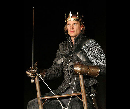 Henry stands at the top of a wooden ladder in his chainmail and crown, carrying a sword