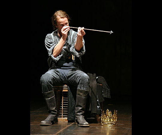 Henry sits examining an arrow, his golden crown on the floor in front of him