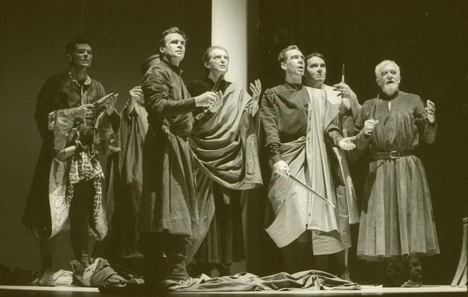 The company of Julius Caesar stand on stage, wearing robes and holding long daggers