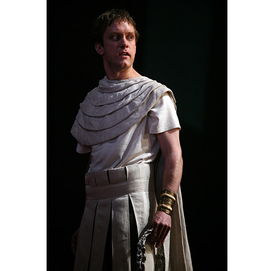 A man stands in white Roman dress