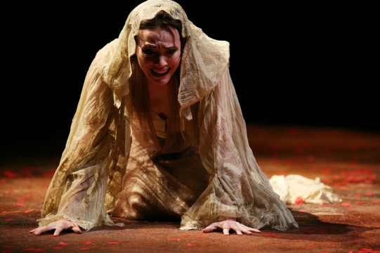 A woman cries on the floor, a shroud over her head