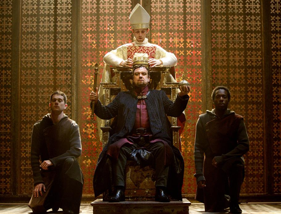A man on a throne holds a sceptre and orb as he is crowned by a cardinal.