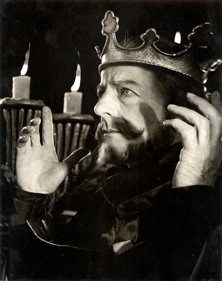 Robert Harris as King John, seated in his crown in front of a two large candles.