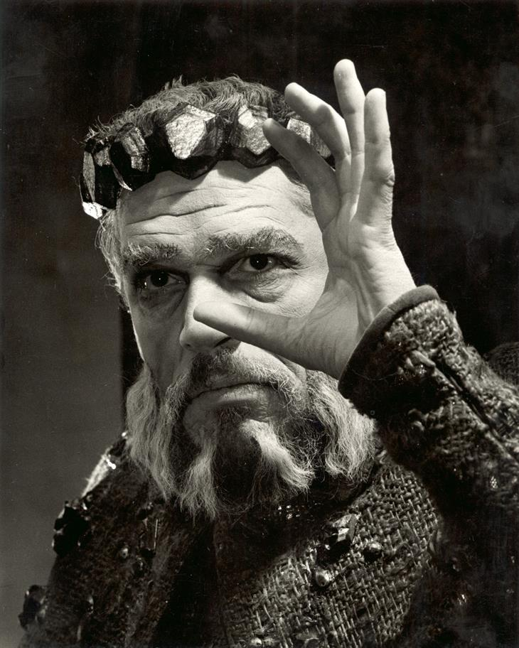 Black and white photo of a bearded Paul Scofield as King Lear holding a hand up to his face and wearing a simple crown