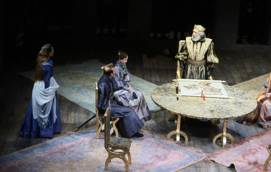 A regally dressed King Lear (Michael Gambon) stands before a golden table on which a map of his kingdom is stretched out