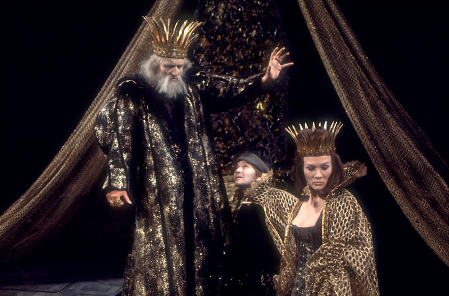 Wearing his golden crown, King Lear (Eric) raises his hand to banish his daughter Cordelia, as the Fool crouches between them