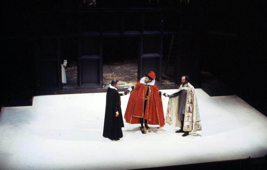 Three men hold hands in the middle of a white stage, the middle one richly dressed in red gown and feathered hat