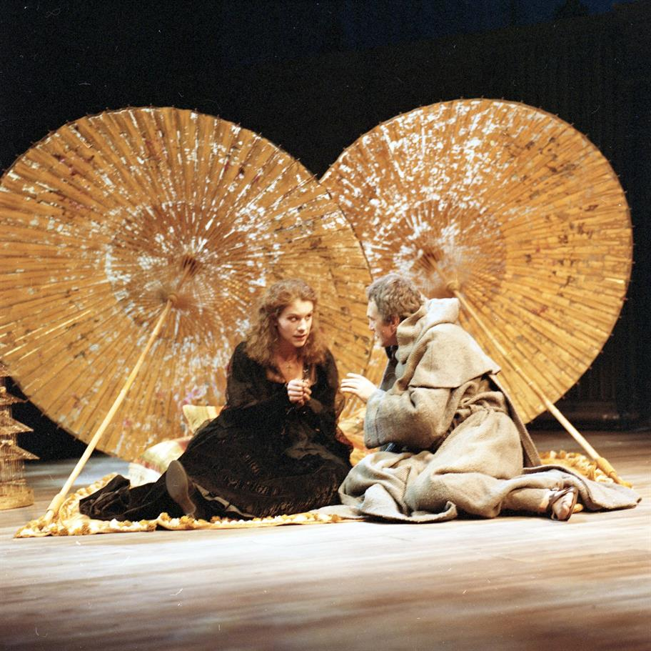 Young woman in black sits on the ground next to friar under two enormous gold-tinted parasols