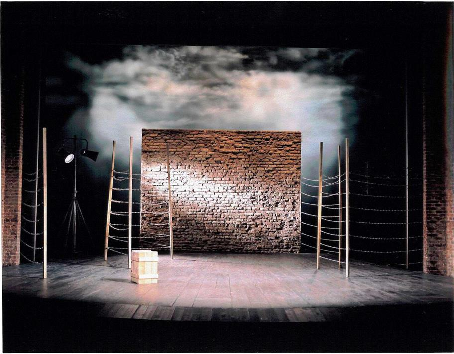 Set position for Measure for Measure 2003 showing prison scene with barbed-wire and brick wall