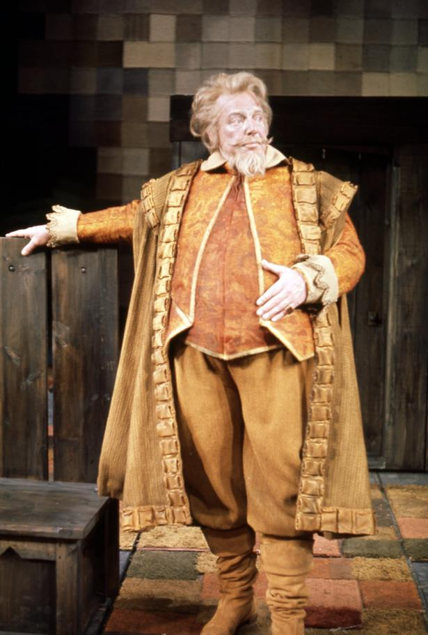 Large bearded elderly man dressed in Elizabethan costume rests one arm on the back of a settle and stares proudly to one side
