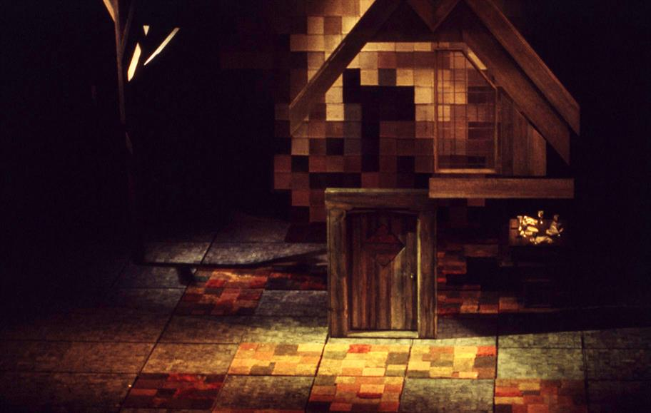 Illuminated theatrical set in autumnal colours showing patchwork floor and wooden door with roof shape abovePhoto by Tom Holte Theatre Photographic Collection (c) Shakespeare Birthplace Trust