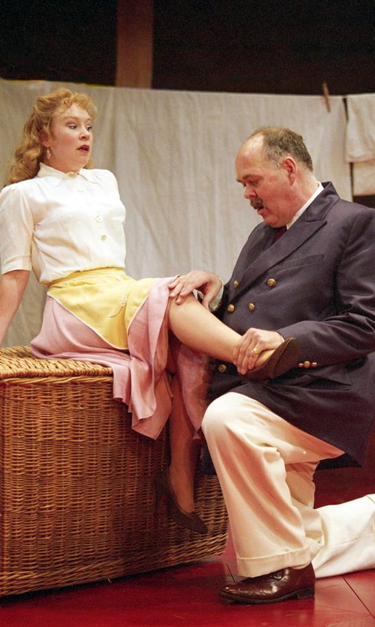 A younger woman sits anxiously on a laundry basket as an older man in white trousers and navy blazer exposes one leg under her skirt