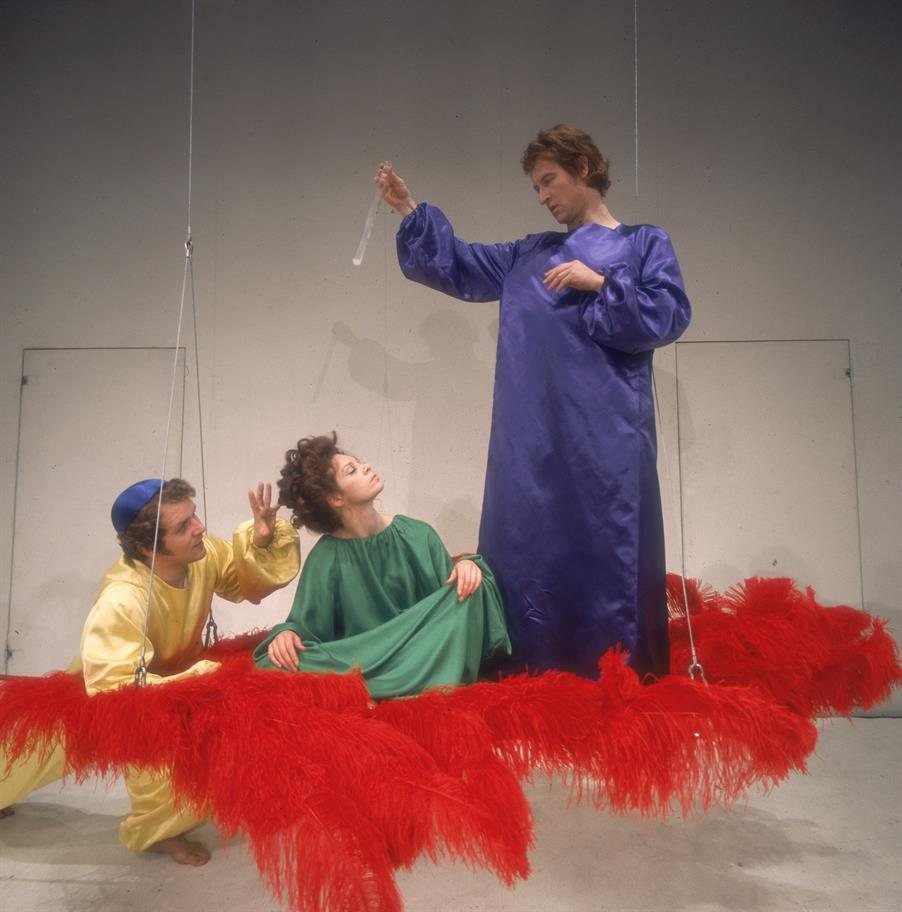 Oberon (Alan Howard, left) casts a spell while Puck (John Kane, right), drops magic potion into the eyes of Titania (Sarah Kestelman).