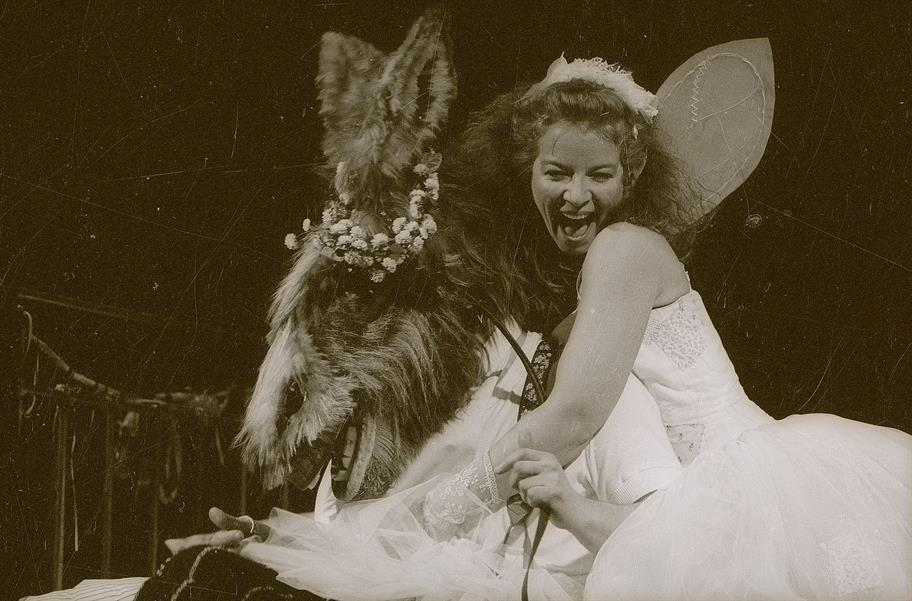 A woman dressed as a fairy hugs an ass with flowers around its ears