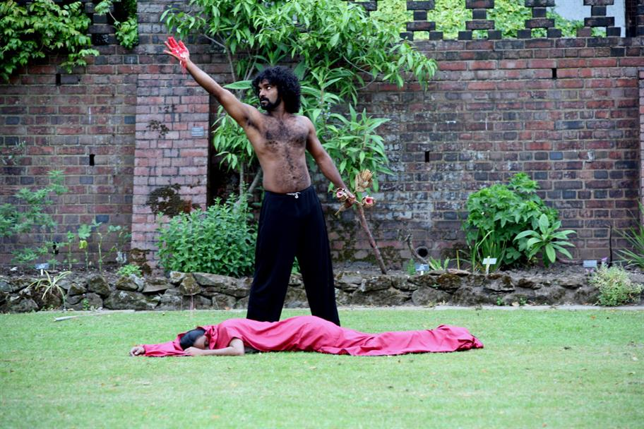 A topless man with a bloodied hand stands over the body of a woman in red