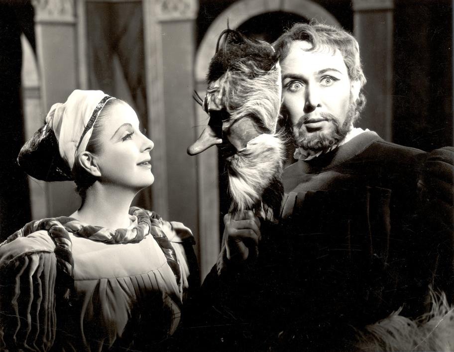 A woman holds a mask against the face of a bearded man