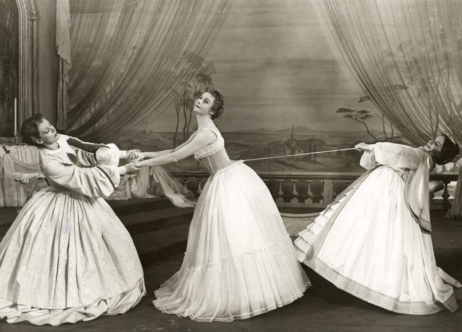 Two women pull at the strings of a lady's corset